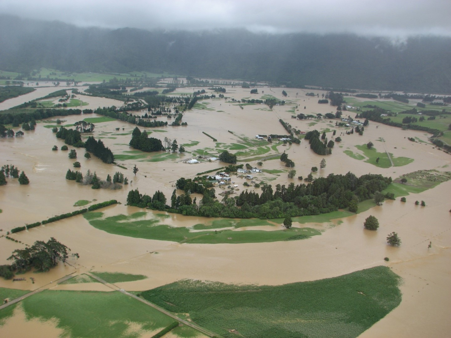 View of the Aorere River in flood covering fields, roads and lapping at houses, in December 2010