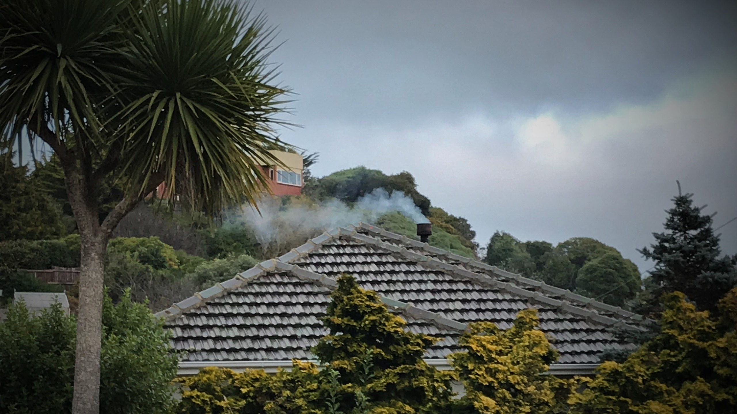 Roof view of a home with fire burning and smoke coming out of the chimney