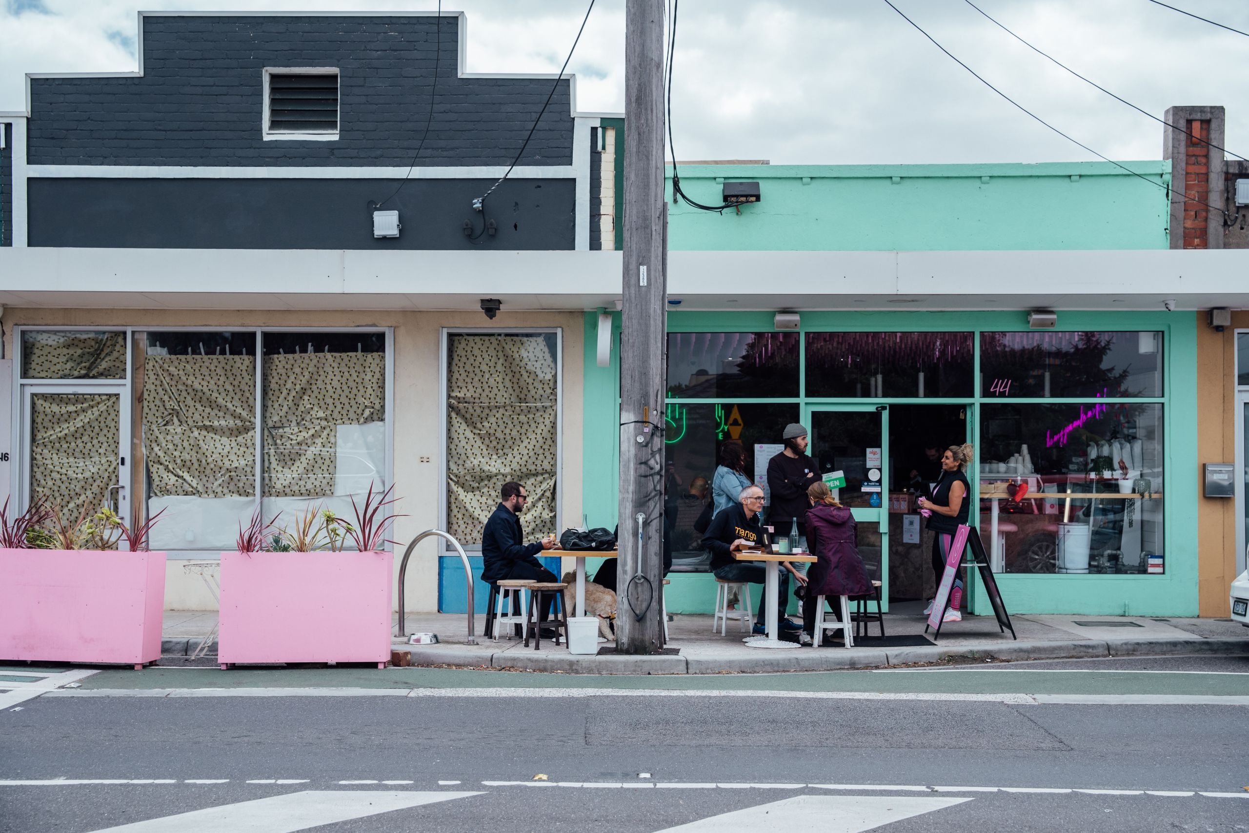 An exterior of a cafe. The awning is mint green and there is a pale pink planter box on the street. People sit outside the cafe chatting and eating.