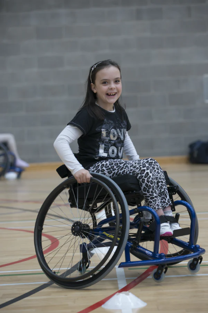 Image of young girl in wheelchair smiling, on basketball court