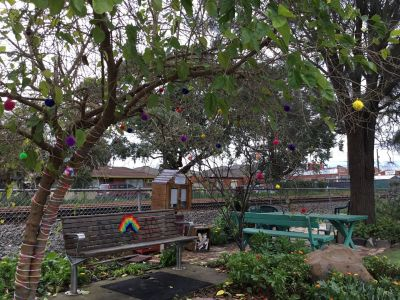 View of a parklet in front of train tracks. There are trees decorated by 'yarn bombing', with colourful pom-poms hanging from branches.