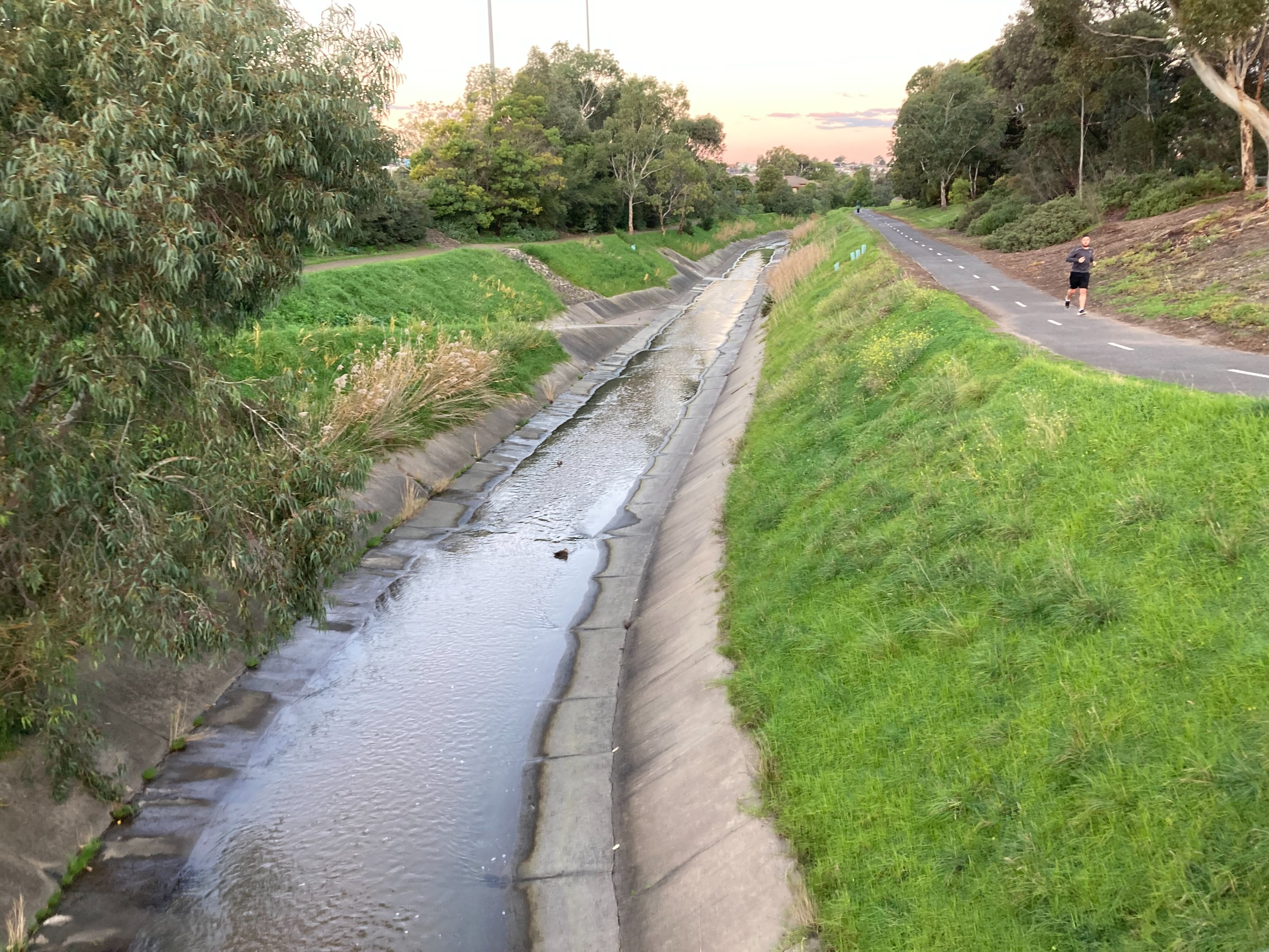 Photo of creek with concrete and grass edging.