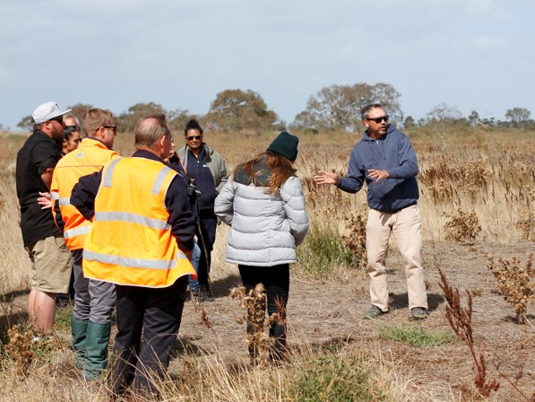 People standing in group at Ryans Swamp whilst another person demonstrates cultural burning practices.