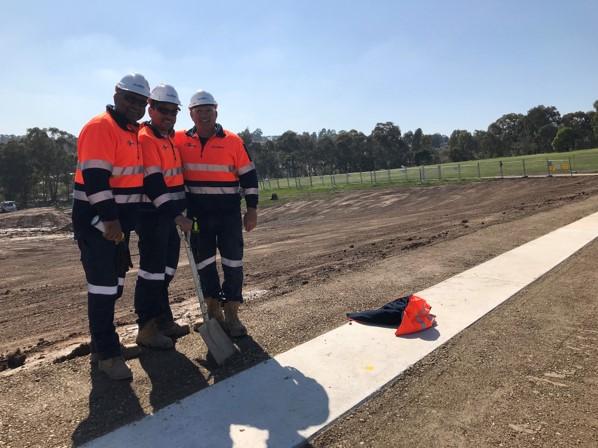 Three people in safety gear standing alongside a pipeline.