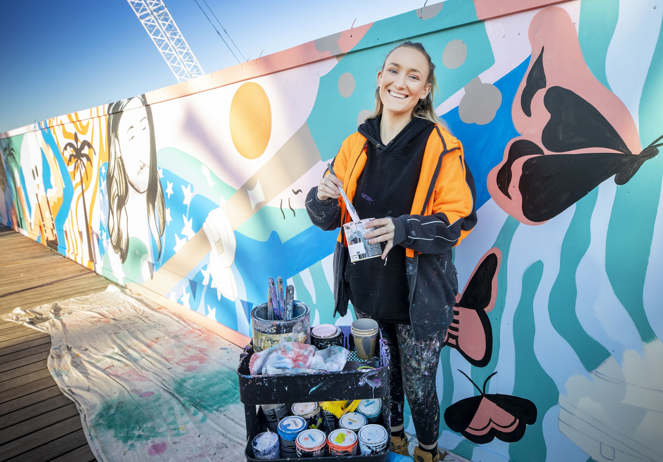 Justine Milsom from Juzpop Creations creating artwork on the timber hoarding around the construction site