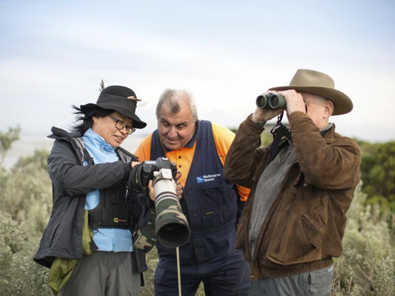 3 people looking together at images on a camera