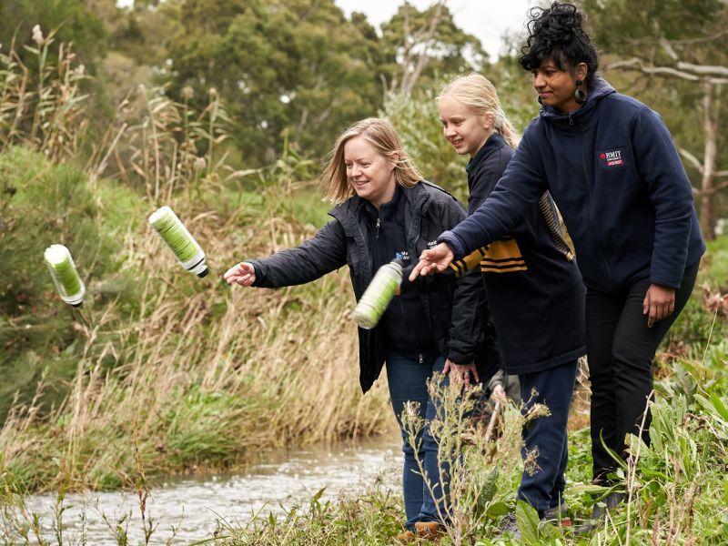 school students throwing litter trackers in creek