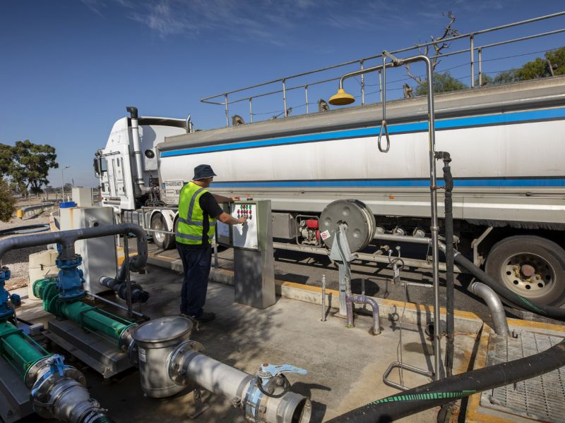 person using controls standing next to a truck with liquid organic waste.