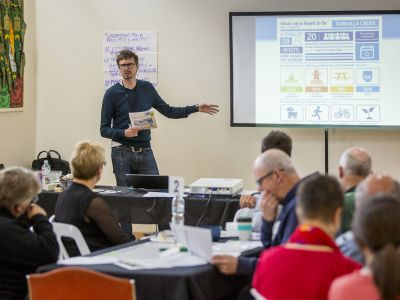 Man presenting concept design to seated Community Advisory Group members