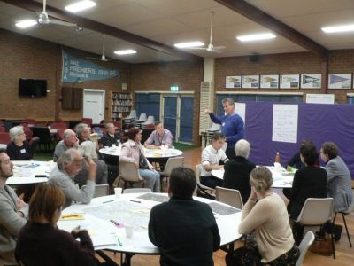 Photo of community sitting at tables for consultation workshop