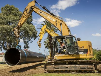 Image showing pipe being lifted from truck using two excavators
