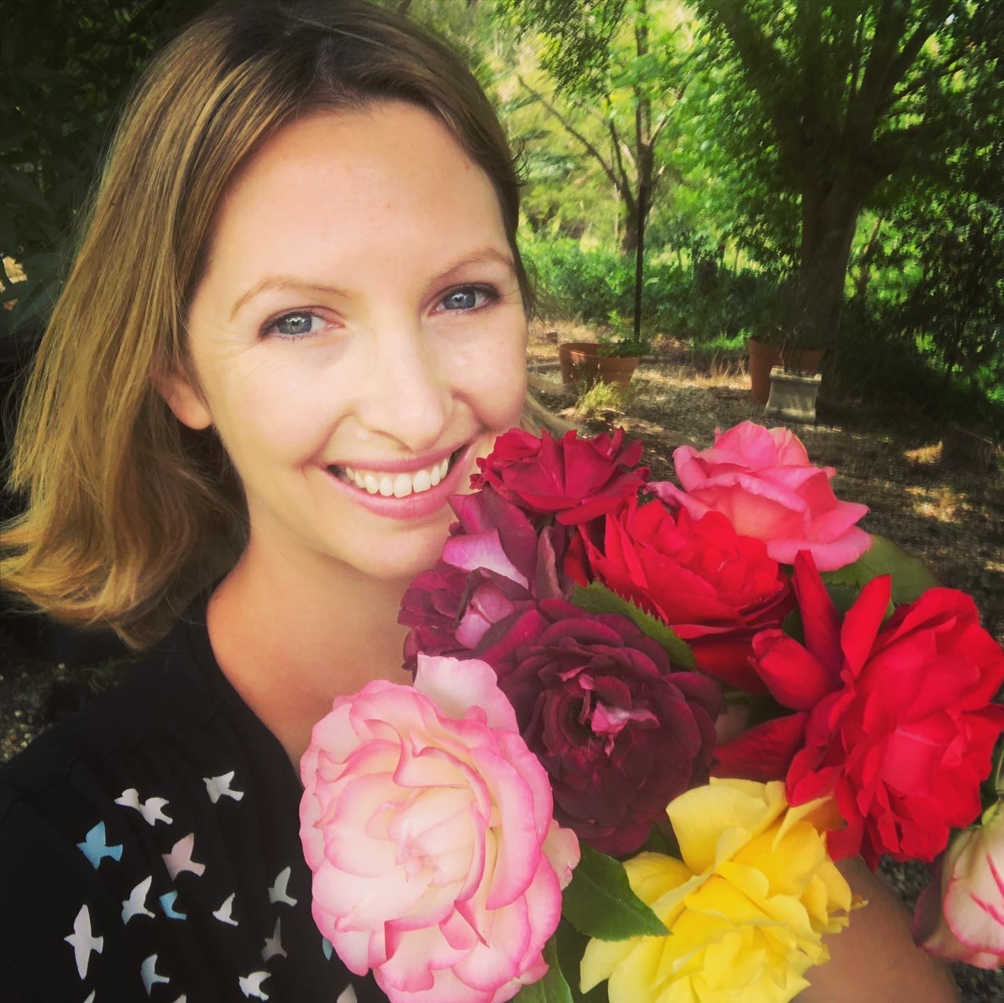 A photo of our site administrator. She is smiling and holding roses from her garden.