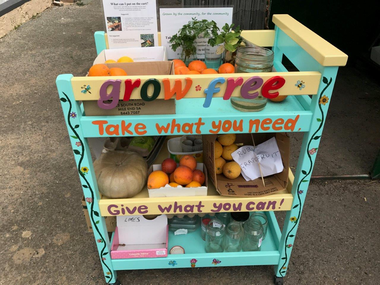 Grow free cart with vegetables, jars and books to share