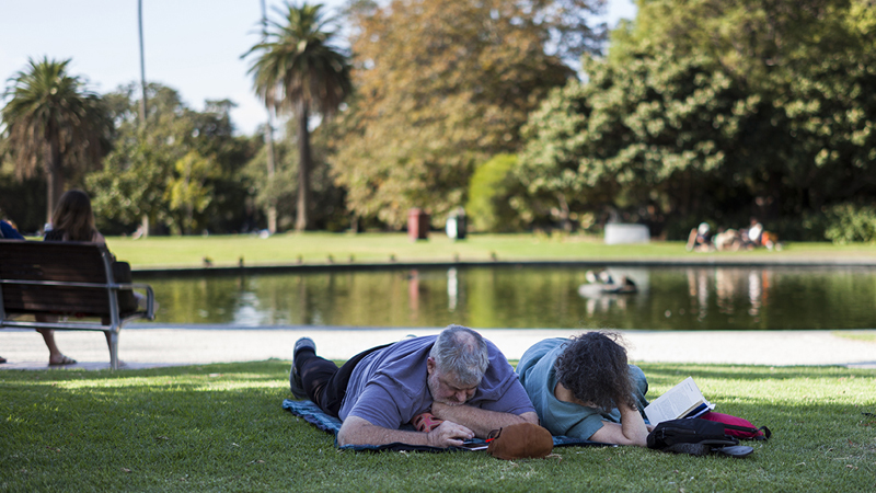 A man and woman lying on the grass in front pond at St Kilda's Botanical gardens