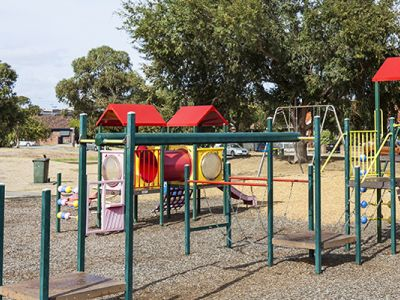 T.T. Buckingham reserve playground showing a section of equipment with monkeybars, balancing bridge and a slide.