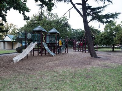 St Vincent Garden junior playground showing slides and static equipment on a tanbark base.
