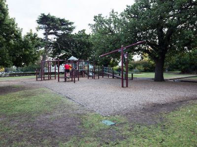 Image showing the playground or older children, including swings, see-saw and tanbark base with trees nearby.