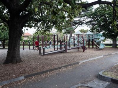 Wide pathways leading to the St Vincent Garden playground with trees on the grassy areas either side.