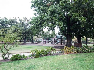 Long view of St Vincent Garden junior play area with swings garden beds and grass areas.