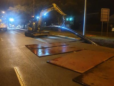 Digger holding HDPE pipe up as it is feed into old water main as part of relining project at night