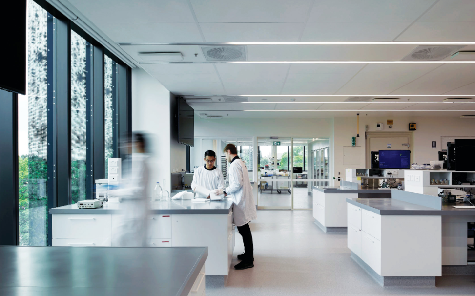 The laboratory shows students in white coats in a research environment with computers in a pristine environment.