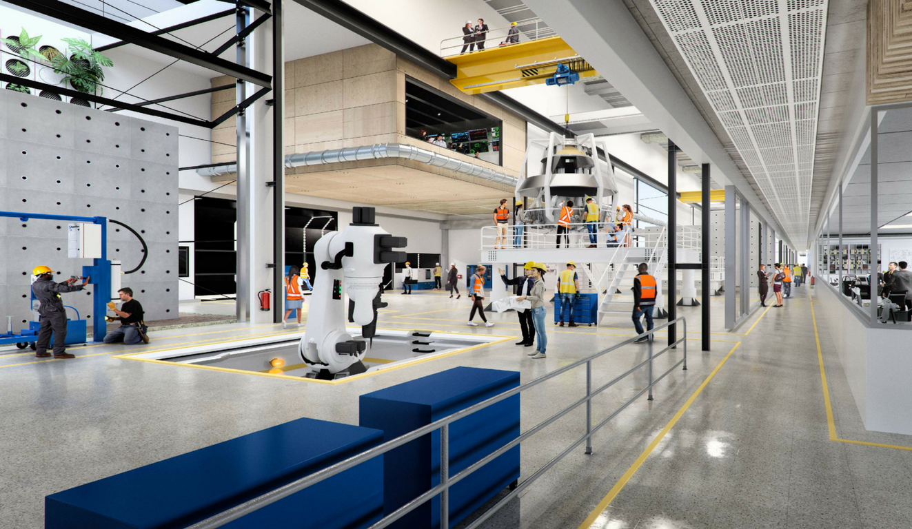 A white robotic arms sits in a modern engineering warehouse with engineers working on welding, assembly and maintenance of a large scale project.