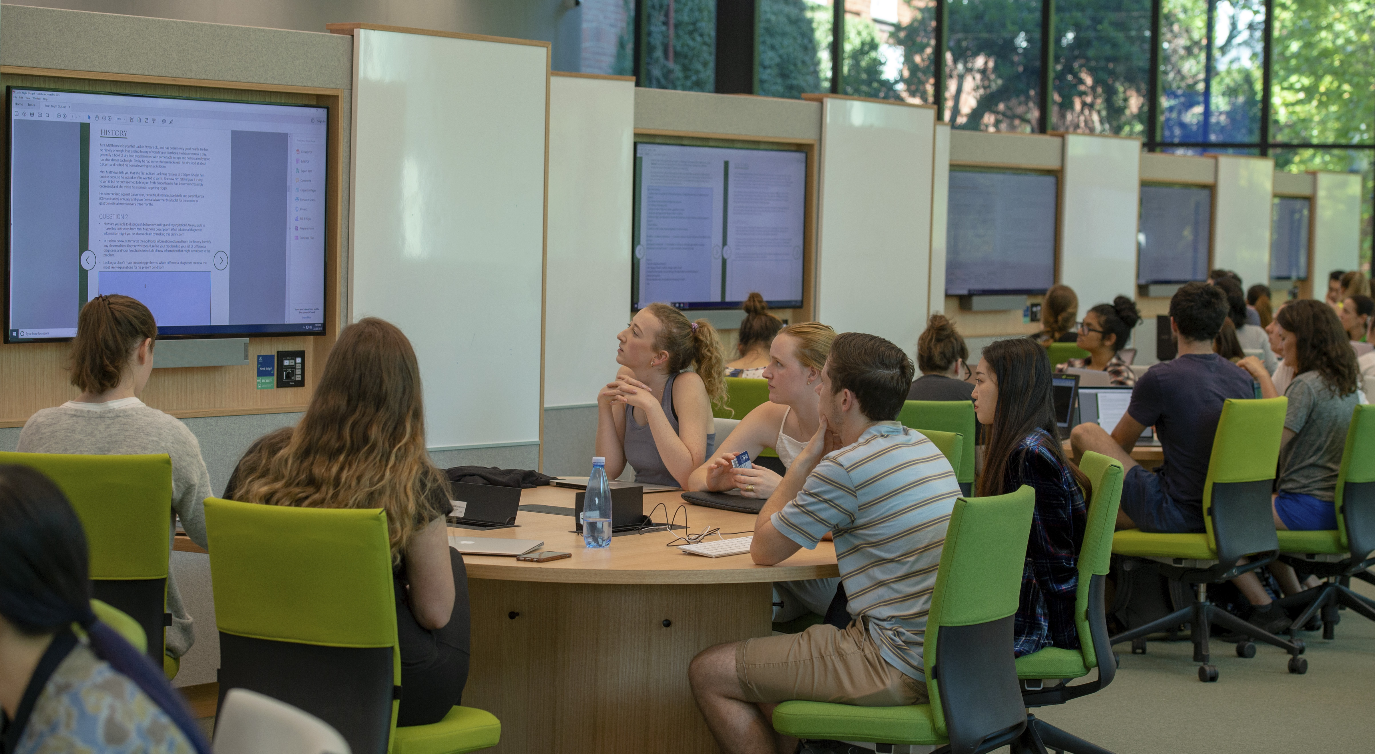 Student sit around a table examining a computer screen in groups with a arrangement that is similar to dedicated pods or sections.