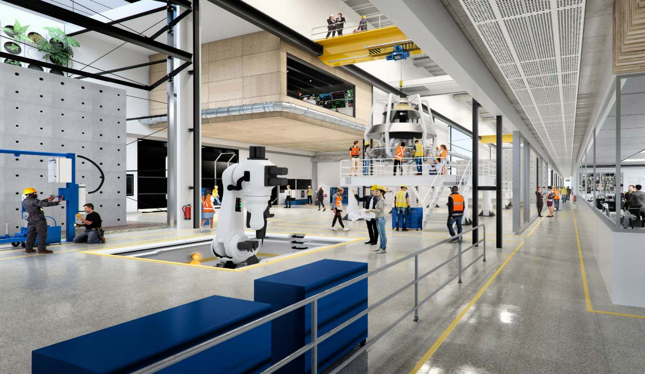 View of the interior of an industrial factory with engineers and builders testing sophisticated equiment including a robotic arm.