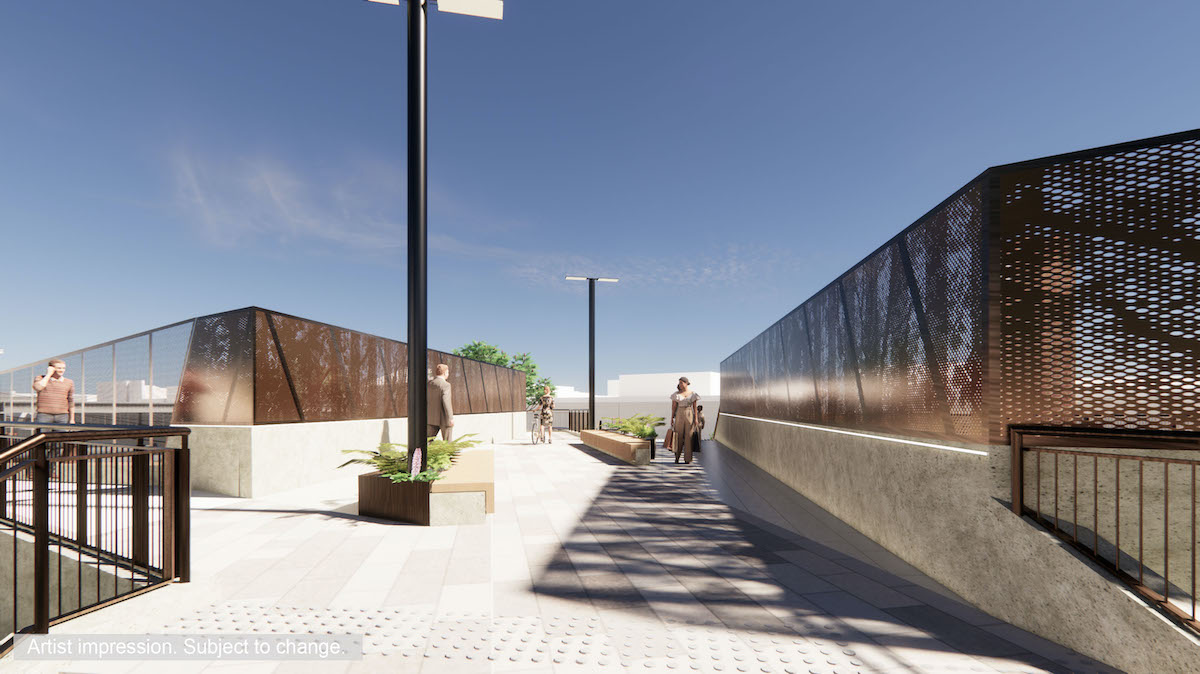 A closer view of the pedestrian bridge includes stairs and ramps for access, landscaping at the base of the bridge and rust coloured screening.