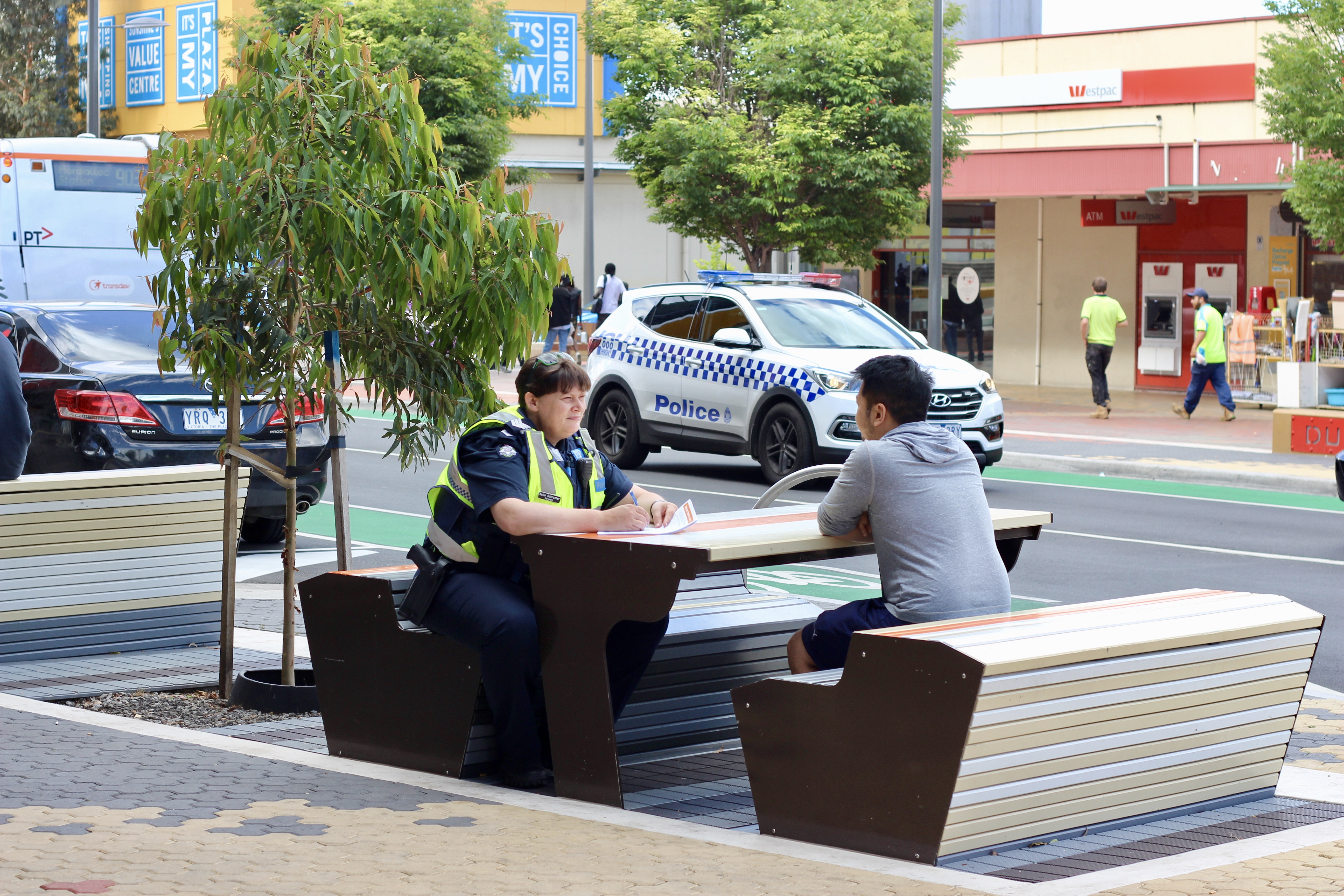 A police officer and a member of the public chat while sitting at an outdoor table.