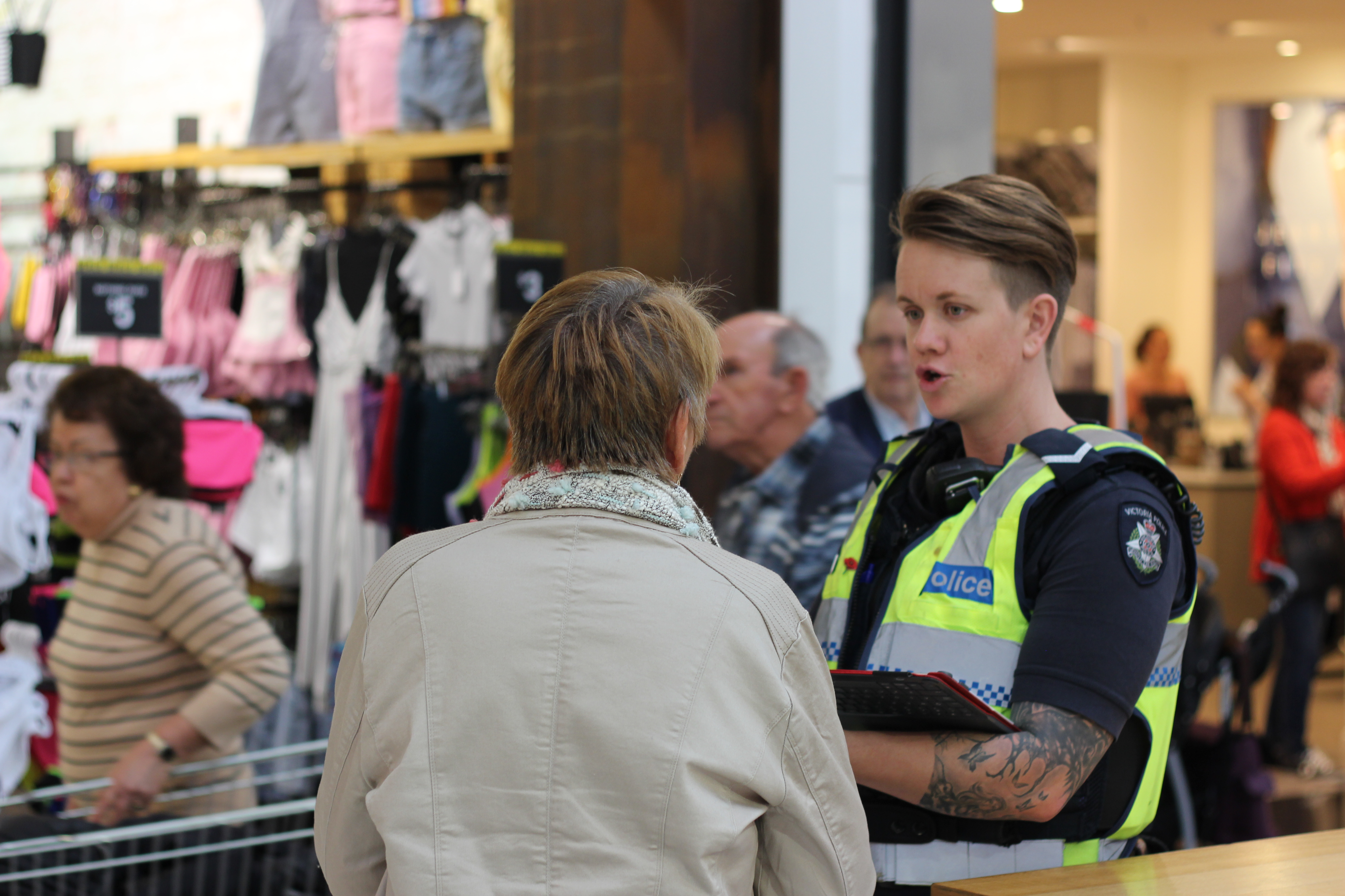 A police officer chats with a woman. They are standing in a shopping centre and there are shoppers in the background.