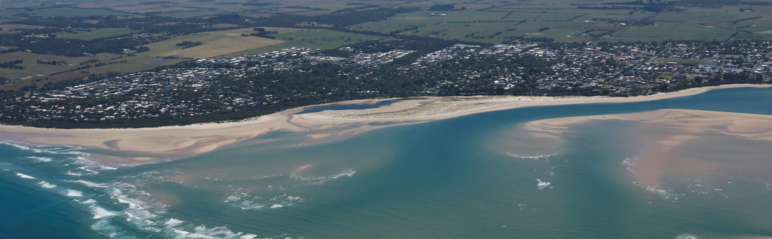Aerial photo of coastline at Inverloch showing wave movement, beach and town