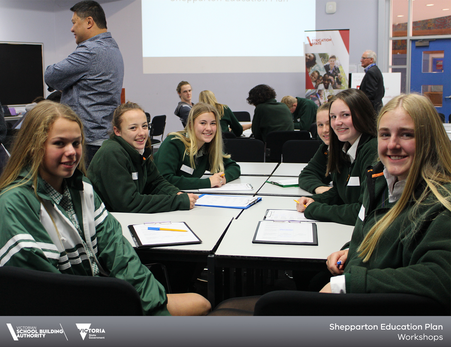 6 smiling girls at table for secondary student workshop