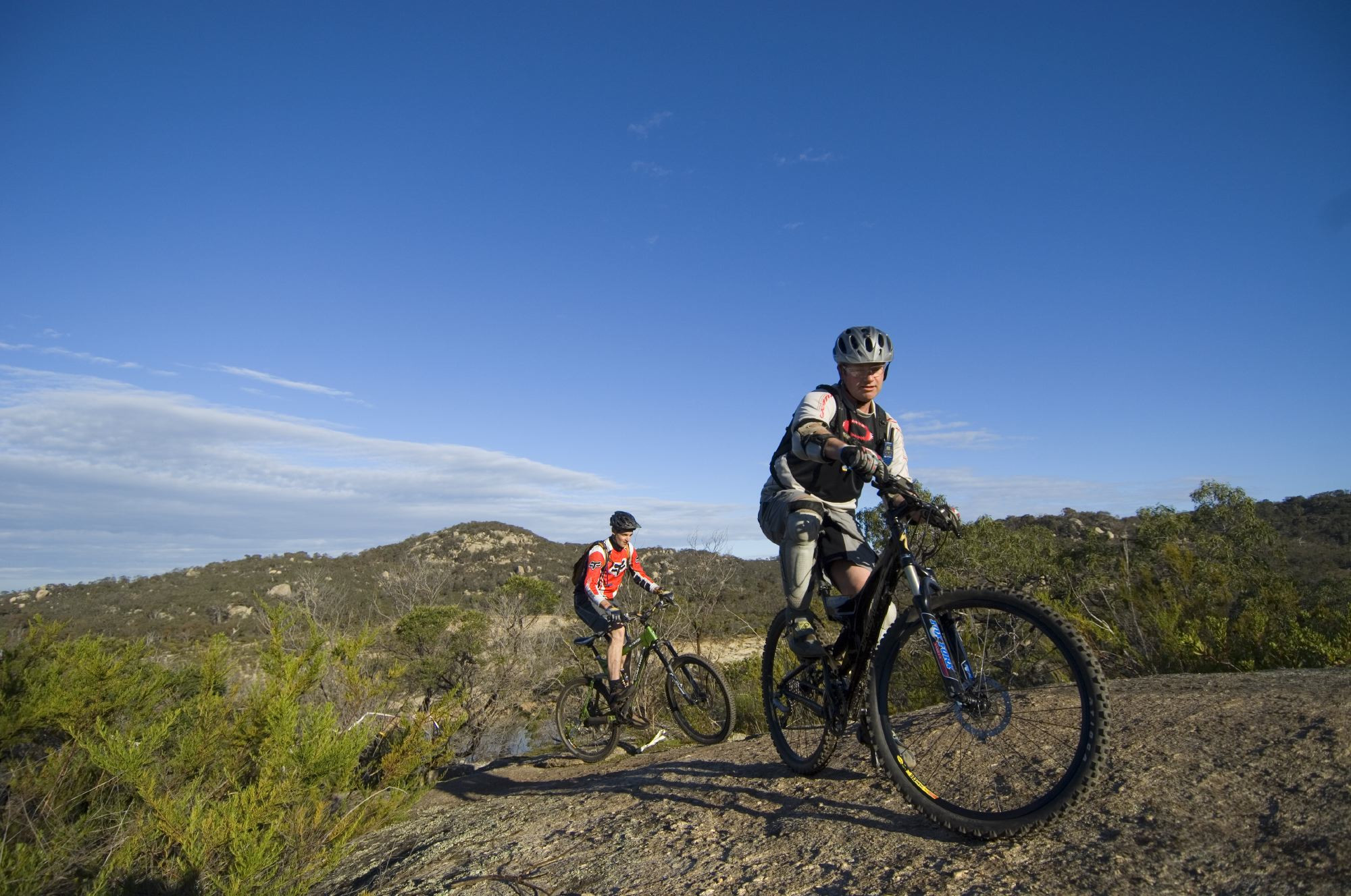 In this image two men ride their bikes over rocks in the You Yangs