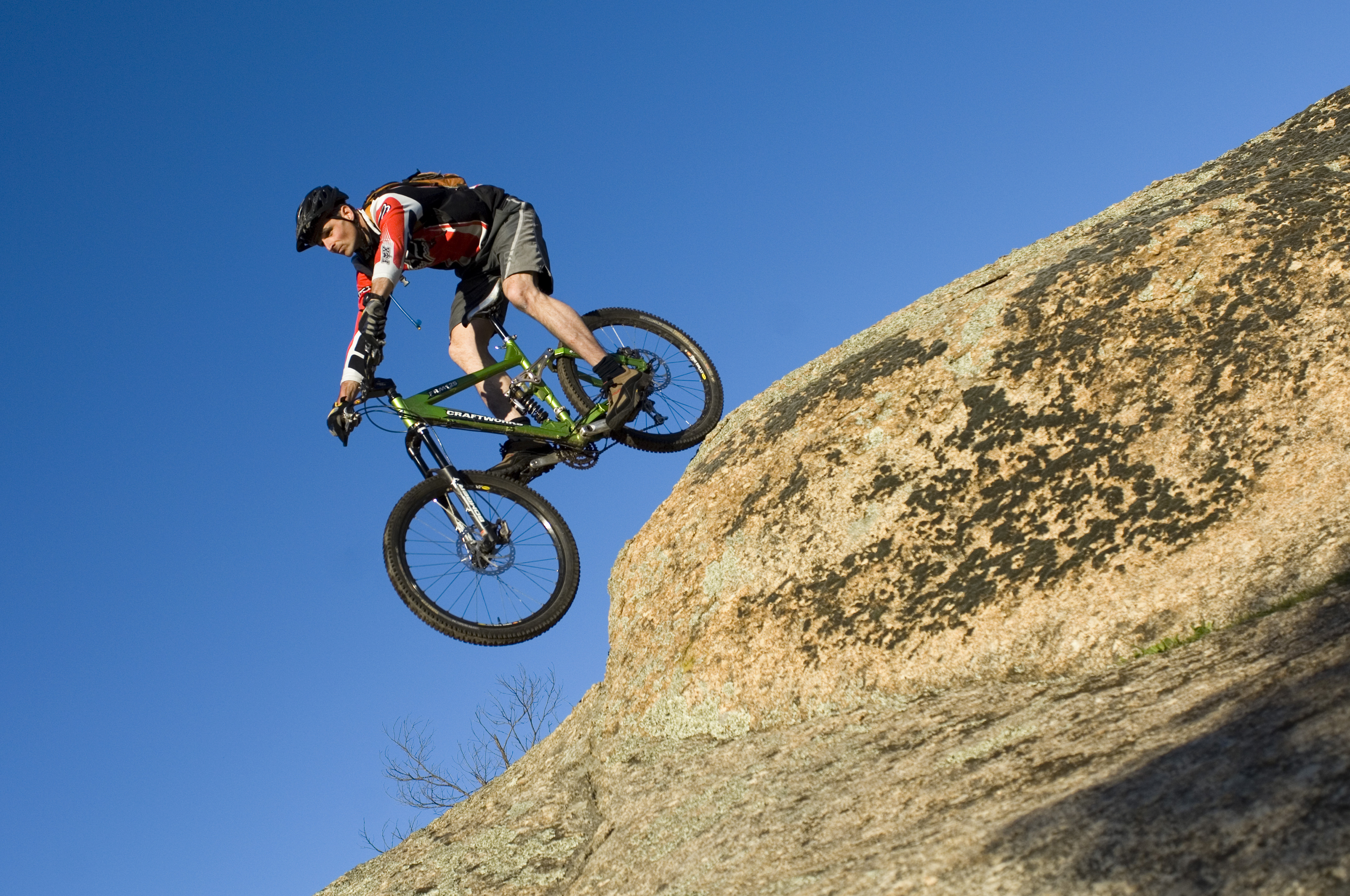 In this image a man rides a bike over a large rock.