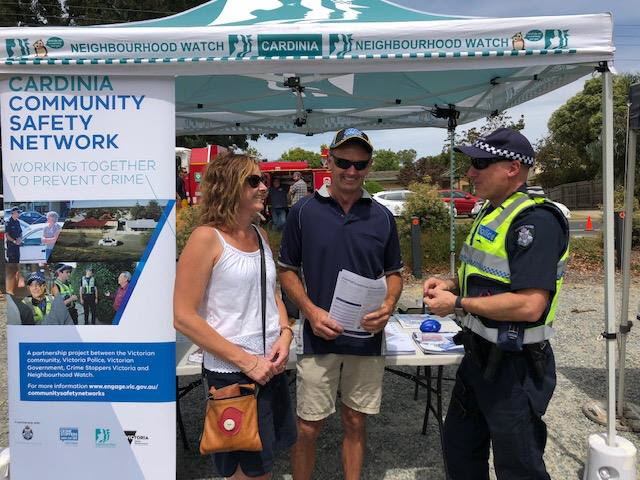 Police officers talking with two members of the public at a community event