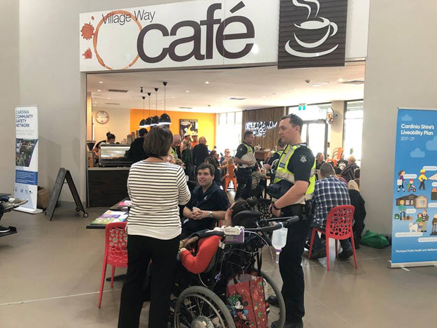 A police officer standing outside a cafe talking with members of the public