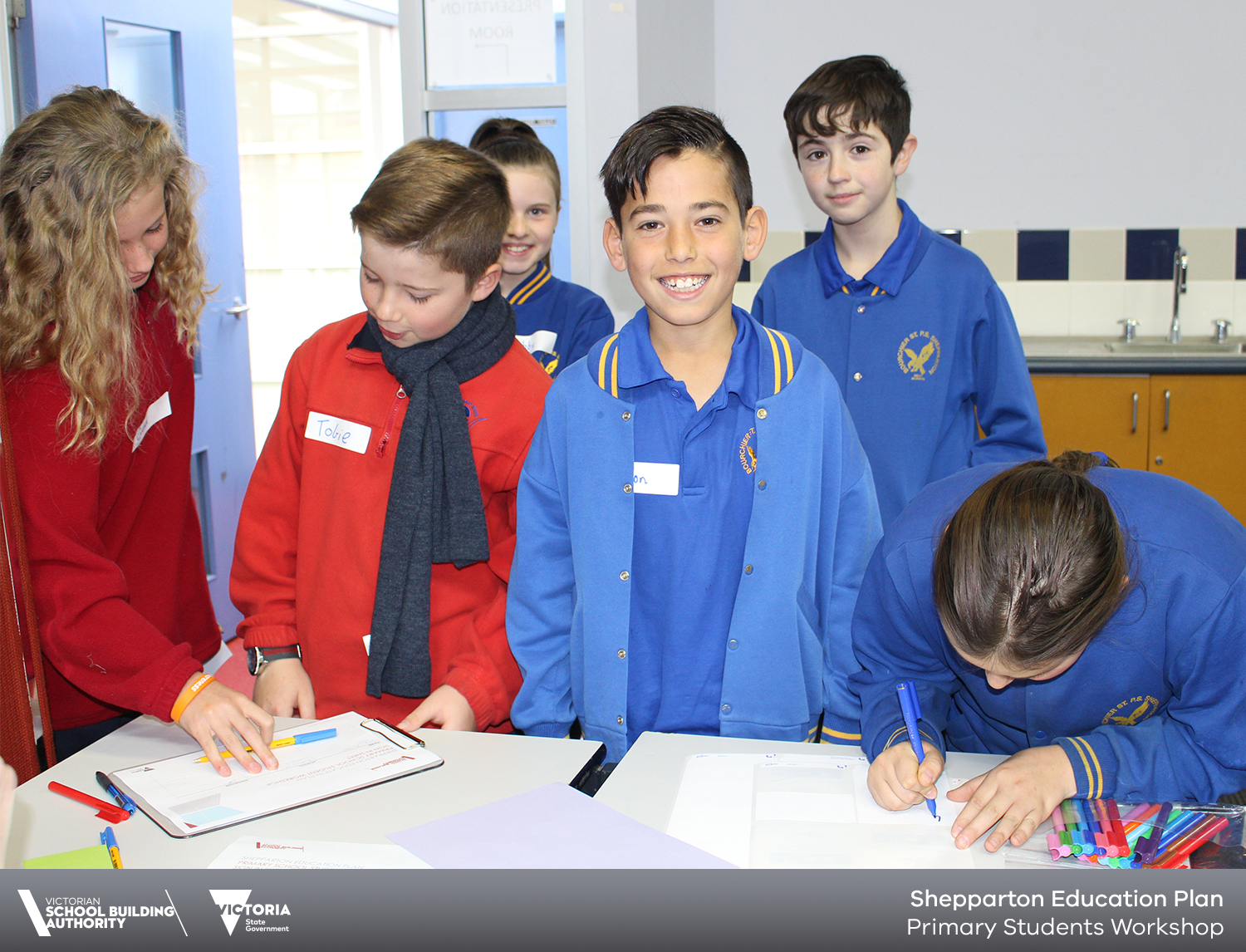 Smiling boy, primary students signing in at workshop