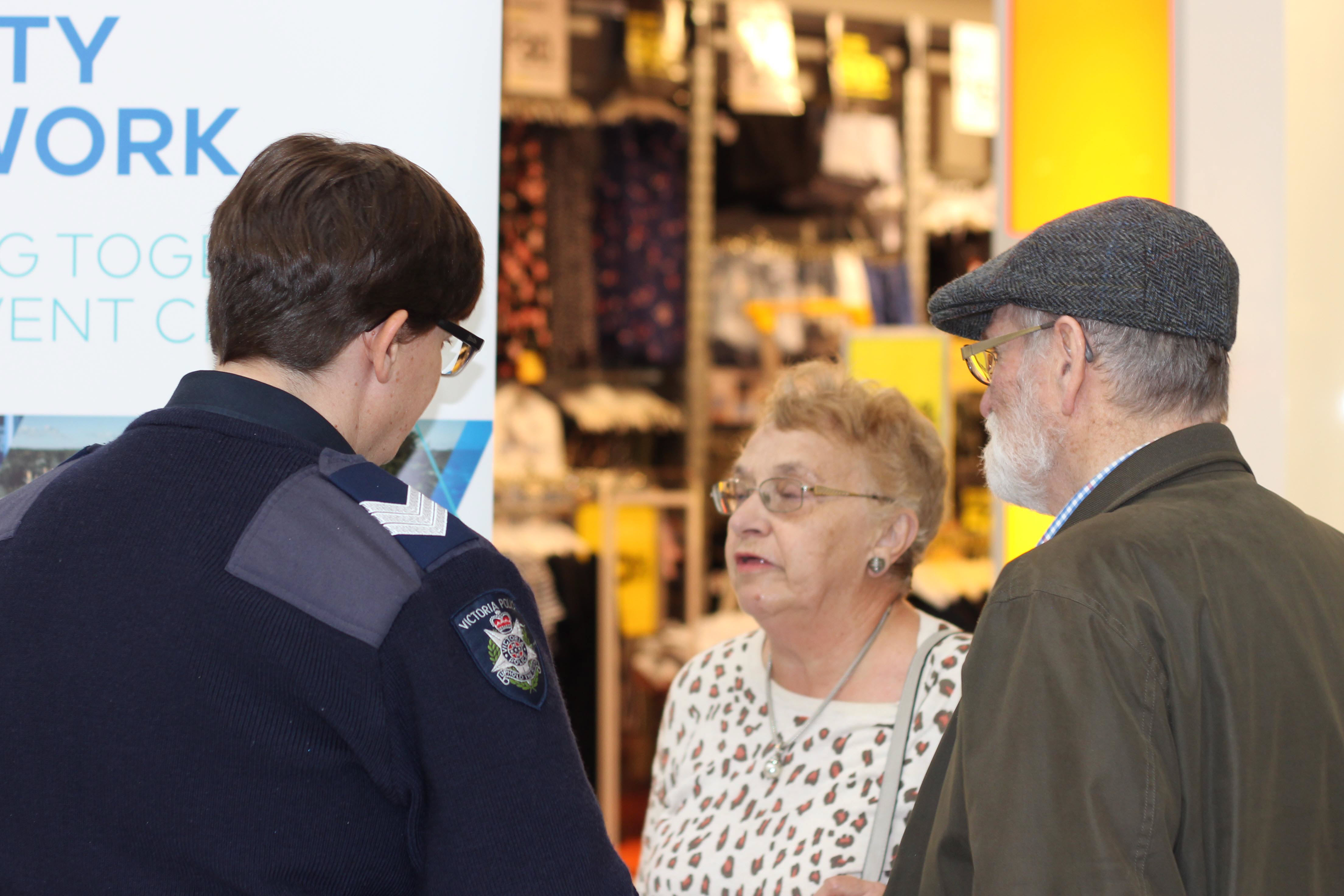 A police officer chats with a man and a woman. The woman is wearing an animal print top and the man is wearing a peak cap and brown jacket