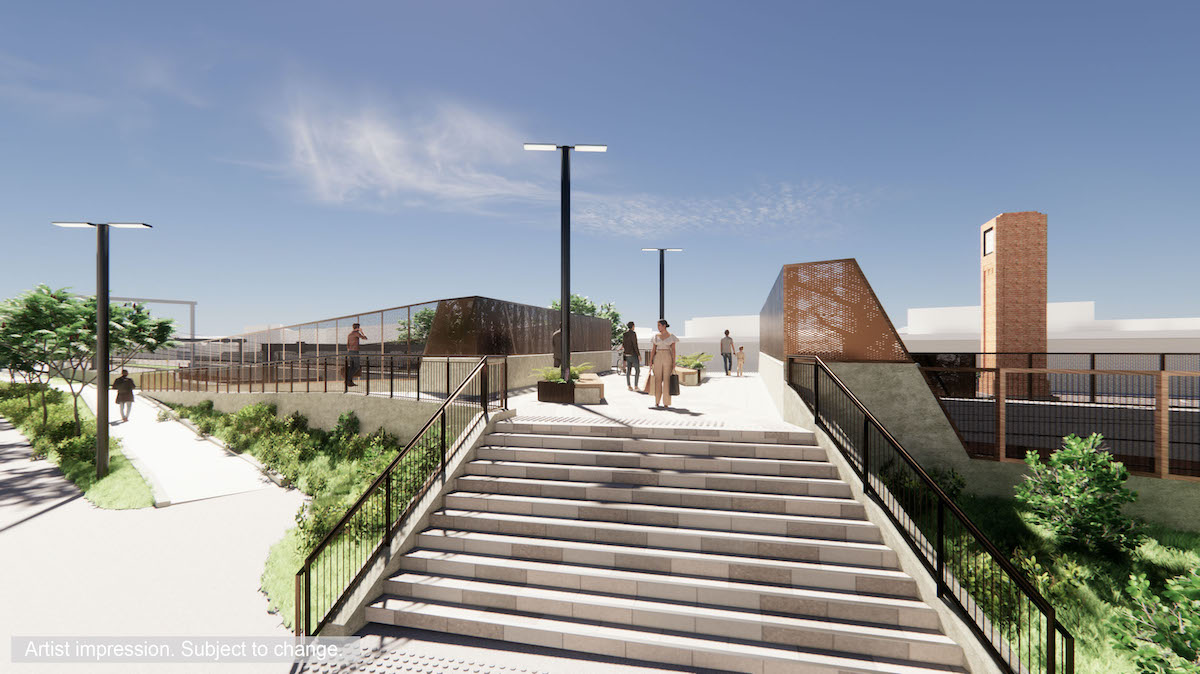 The new pedestrian bridge includes stairs and a ramp from the left side, and rust coloured screening along the bridge.