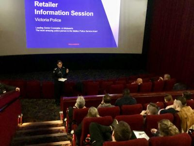 Police officer presenting to local retailers