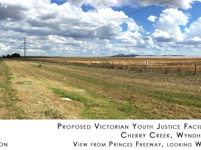 Proposed Victorian youth justice facility. Cherry Creek, Wyndham. View from Princes Freeway, looking west. Artist's impression with trees around facility. Unobtrusive low line of building block about 700 metres from road on open grass paddock.