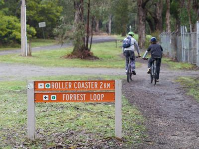 Picture of the Rollercoaster and Forrest loop trail signs with track and fence and 2 riders