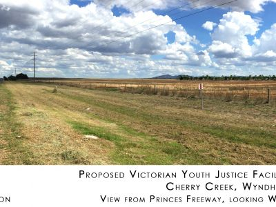 Proposed Victorian youth justice facility. Cherry Creek, Wyndham. View from Princes Freeway, looking west. Artist's impression with trees around facility. Unobtrusive line of trees about 700 metres  from road on open grass paddock.