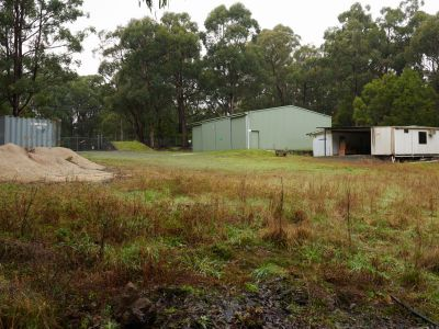 """Old forrest camp showing small pile of gravel, gate, big green shed and old """"Atco"""" hut"""