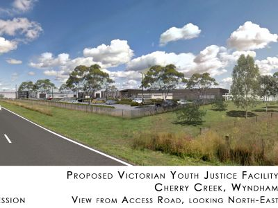 Proposed Victorian youth justice facility. Cherry Creek, Wyndham. View from access road, looking north-east. Artist's impression. Low flat buildings, security walled area, car park and trees close to access road.