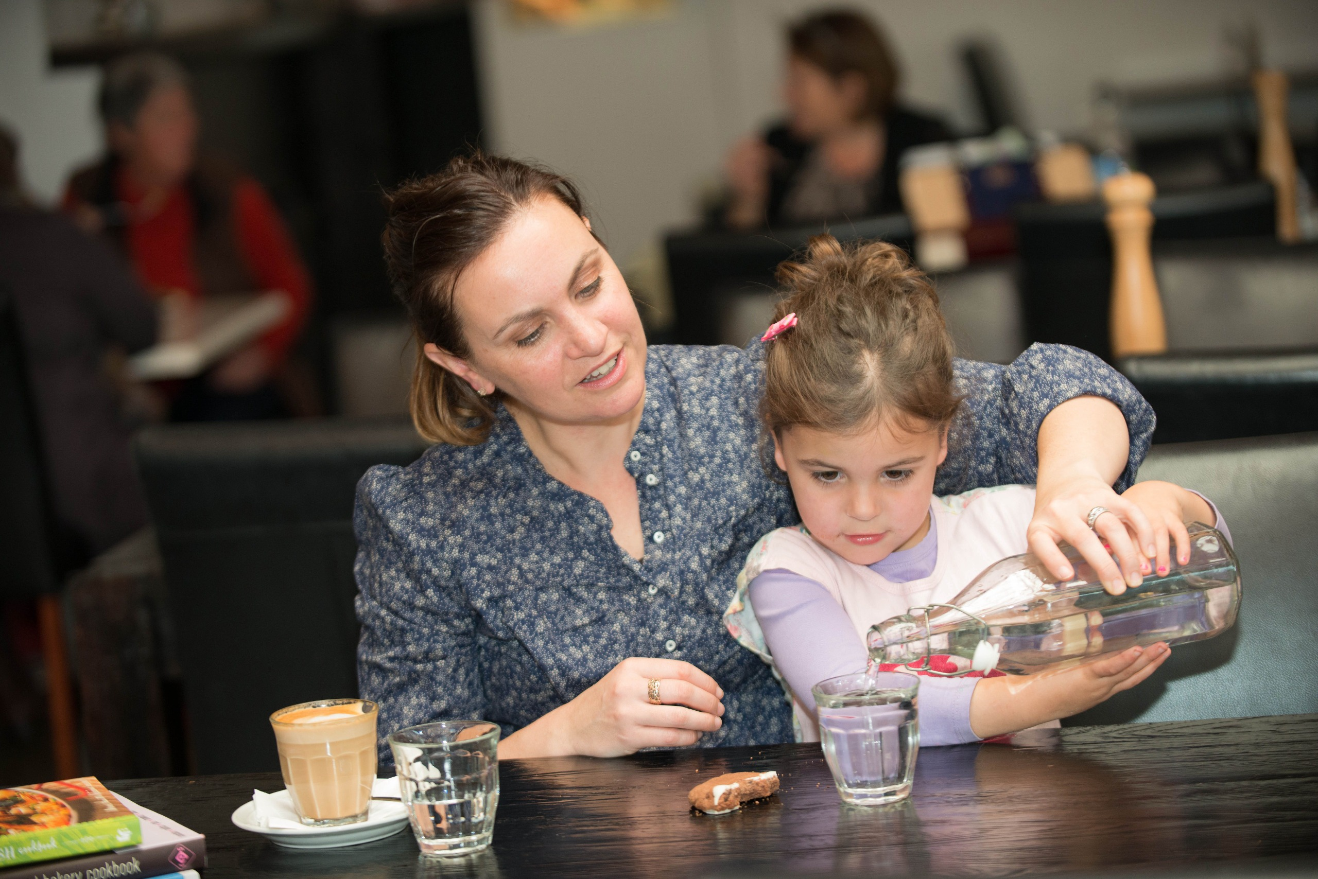Mother and child at a cafe drinking water