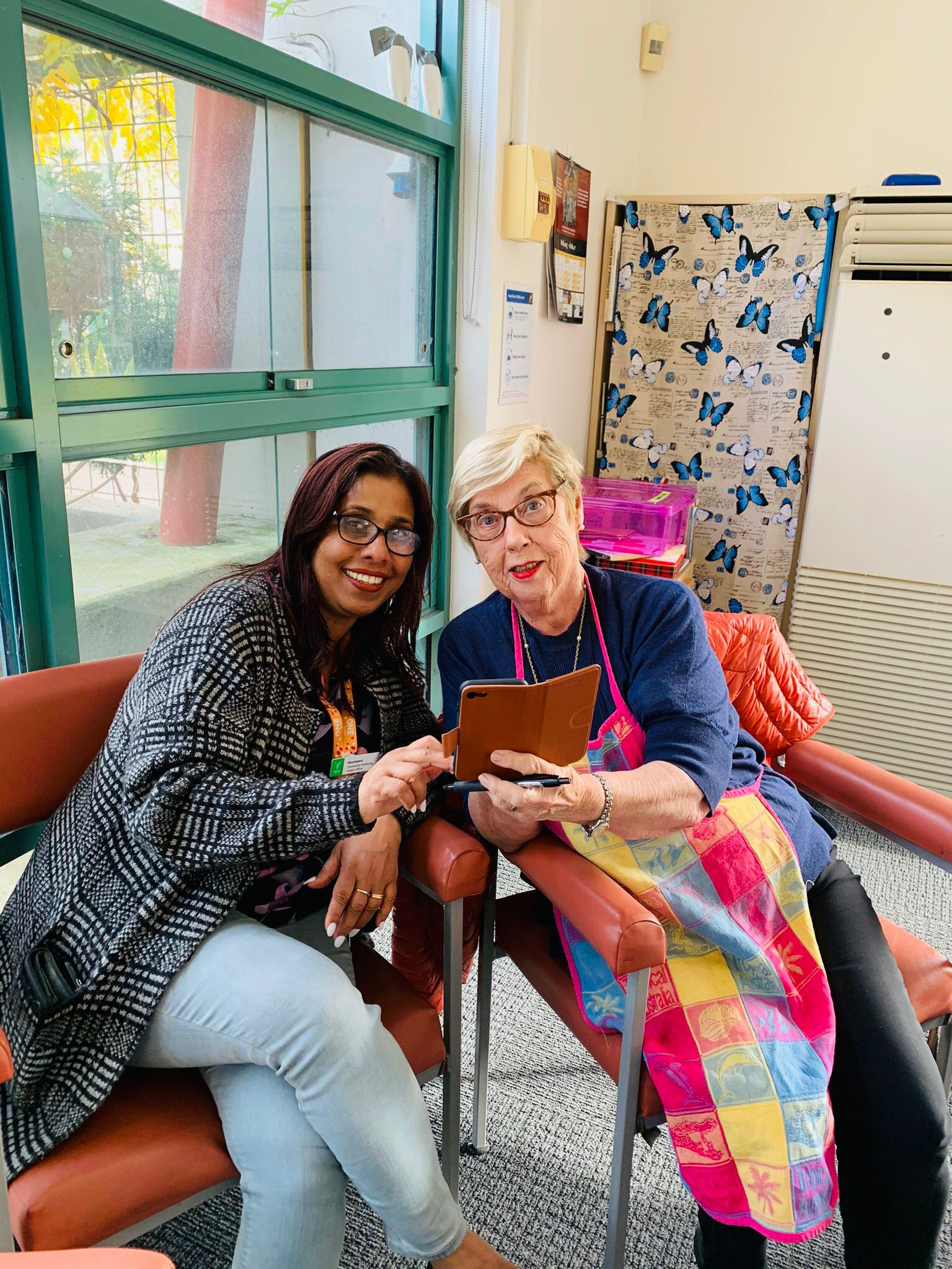 outreach worker teaching older person with Iphone