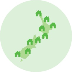 Green vector graphic of the outline of New Zealand with house symbols scattered across it