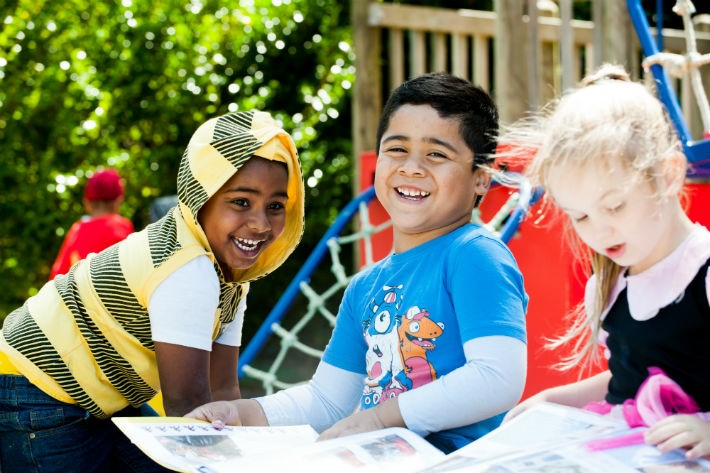 Photograph of smiling children sitting outside